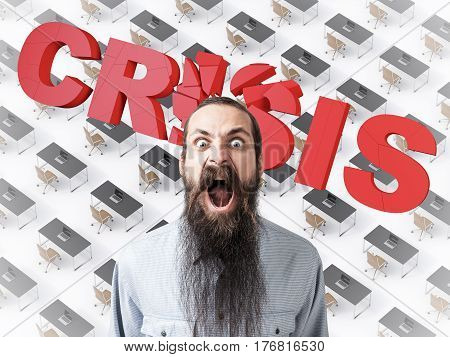 Portrait of a screaming businessman with a long beard. He is standing against a row of desks and a word crisis.