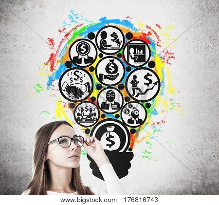 Side view of a young businesswoman in glasses standing near a concrete wall with a money making idea sketch on it.
