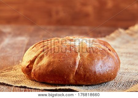 One white bread with flour on a wooden background. Advertising bread. Leaning flour. Bread on the cloth linen. Brown table. Round bread.