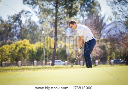 Close Up View Of A Golfer Playing A Chip Shot On A Golf Course In South Africa With Back Light.
