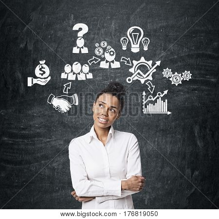 Portrait of a smiling African American businesswoman standing near a blackboard with business icons drawn on it.