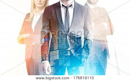 Business trio in a blue and orange city. Close up of two businessmen and a businesswoman standing together against a cityscape. 3d rendering double exposure toned image