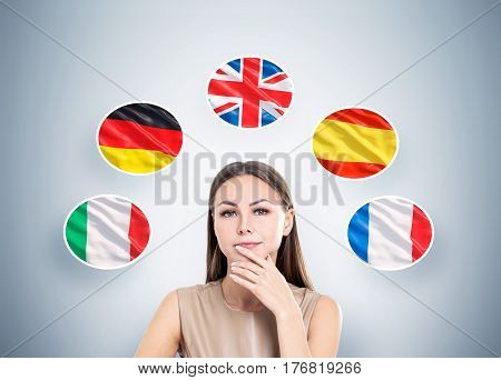 Portrait of a pensive woman in beige clothes standing near a gray wall with and five national flags around her.