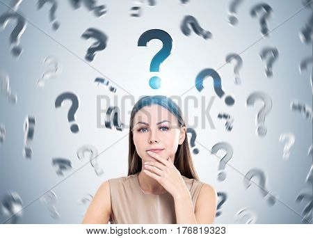 Portrait of a pensive woman in beige standing near a gray wall with question marks falling down. Concept of too many questions