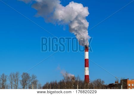 High pipe thermal power plant on the background of blue sky fog smog and out clouds of thick smoke pipe red-and-white it's cold outside.