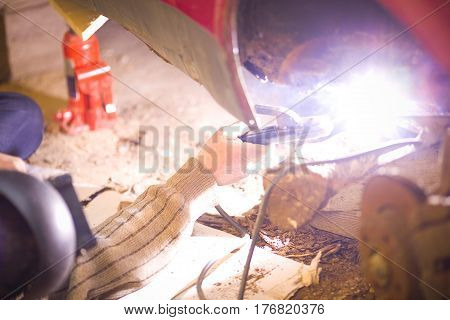 A man is fixing his rusty car with welding.