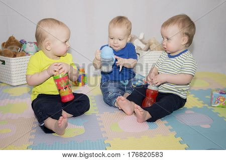 Trio lovely boys sitting and playing with water bottles. Horizontal shot. Concept of friendship