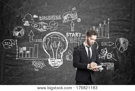 Portrait of a young bearded businessman wearing a black suit and working at a business idea near a blackboard