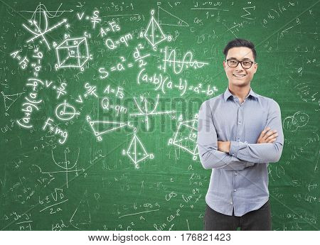 Portrait of a cheerful Asian man standing with crossed arms near a green chalkboard covered by math formulas.