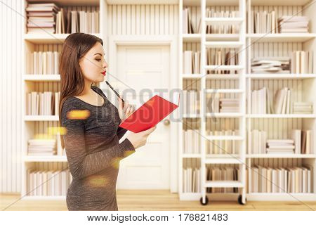 Side view of a young woman holding a red book and standing in a library. Concept of the pleasure of reading toned image.