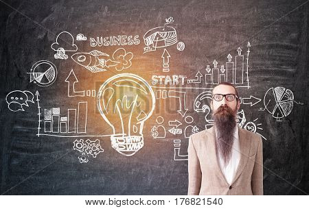 Portrait of a businessman with long beard wearing a beige suit and standing near a blackboard with a business idea sketch on it.