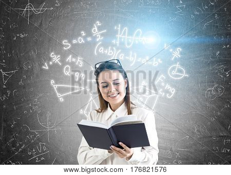 Portrait of a young woman holding a book and standing near a blackboard with formulas on it. Blue flare