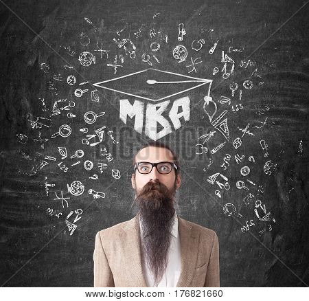 Portrait of a businessman with a long beard and glasses standing near a chalkboard with an MBA sketch on it.