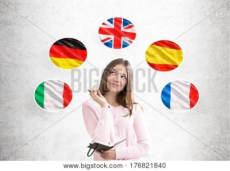 Portrait of a young woman wearing a pink cardigan while standing near a concrete wall with European country flags drawn on it.