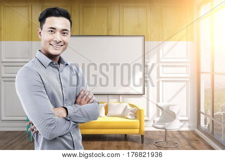 Portrait of a happy Asian businessman standing in an office with a blank whiteboard hanging on a yellow wall. Mock up