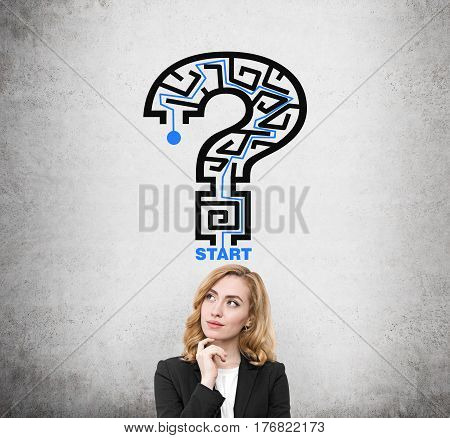Portrait of a red haired businesswoman standing near a concrete wall with a question maze drawing on it.