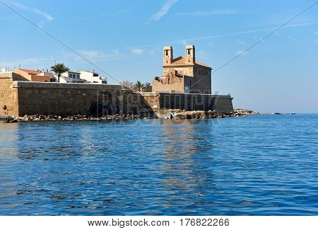 Waterside view to the Church of St. Peter and St. Paul in the Island of Tabarca. Spain