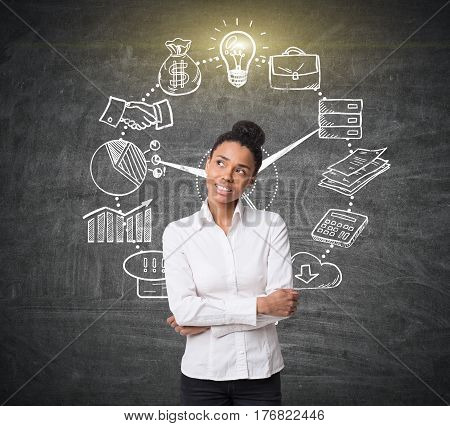 Portrait of an African American girl standing near a blackboard with a business clock sketch on it.