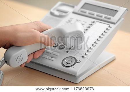 Hand of man with picked up receiver dialing telephone number in office