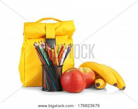 Holder with colorful pencils, lunch bag and fruits on white background