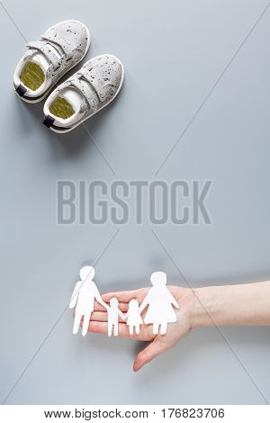 Adoption concept with baby shoes and application on gray table background top view mock up