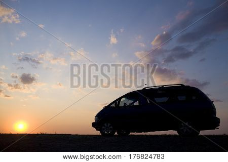 Silhouette of a car on a sunset sunset background.