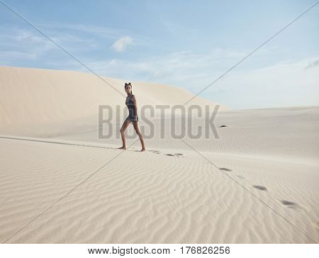 young pretty woman in white sand dunes like a goddes of darkness, fashion diva the dessert
