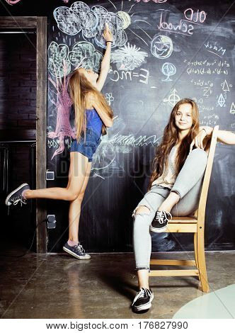 back to school after summer vacations, two teen real girls in classroom with blackboard painted together