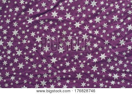 top view of wrinkled background texture of purple textile table cloth with white stars