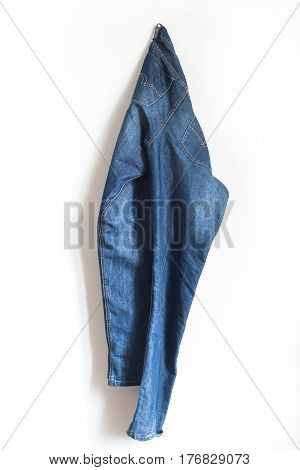 vertical front view of a pair of blue jeans male pants hanging on a white wall