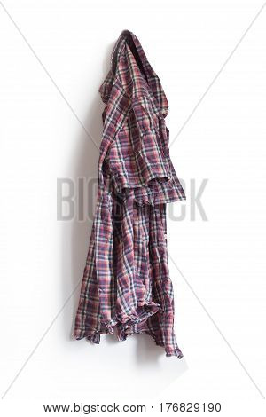 vertical front view of checkered shirt hanging on a white wall