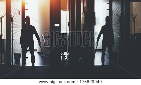 Silhouette of boss or businessman standing in dark office interior with a lot of reflections near meeting rooms and holding katana sword like japanese samurai warrior ready to defence or fight