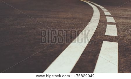 Close up low view of white curved city road marking on asphalt with one continuous line and another dotted line on summer day with copy space for your advertising text message or promotional content