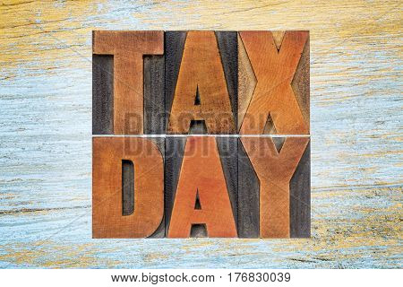 tax day word abstract - text in vintage letterpress wood type against grunge wooden background