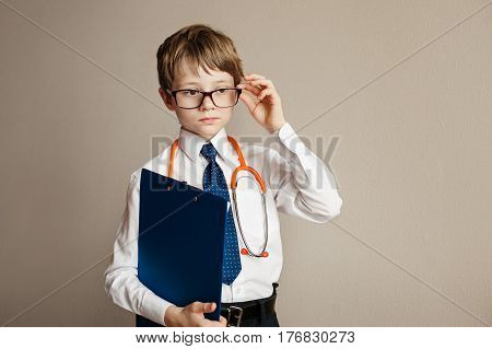 Little scientist smiling and looking at the camera. Gray background.