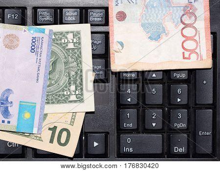 Kazakh tenge and dollars on a laptop keyboard .