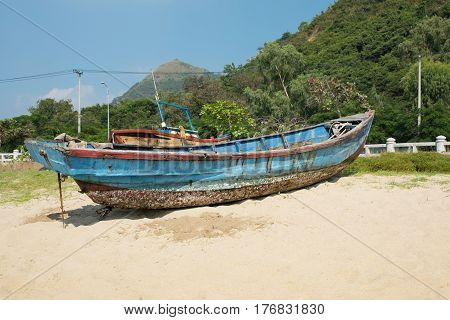 Broken yacht on the seashore. Old blue boat on the sand near the sea or the ocean