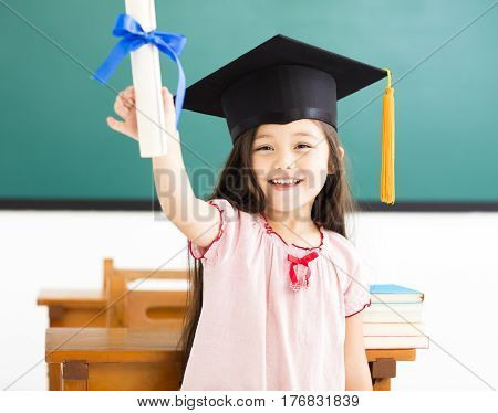 Portrait of cute schoolgirl with graduation hat in classroom