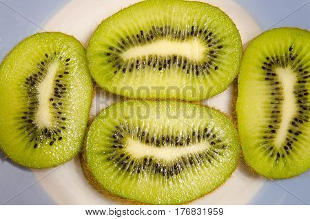 The fruit of the kiwi is cut into flat slices.