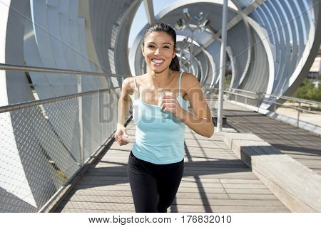 young beautiful and athletic sport woman running and jogging in urban training workout crossing modern metal city bridge in female runner body care and healthy lifestyle concept