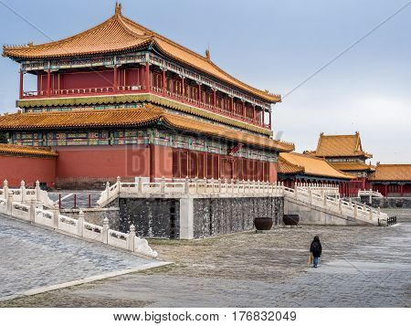 Beijing, China - Oct 30, 2016: Side view of the majestic Tower of State Benevolence building in the Forbidden City (Gu Gong, Palace Museum). Person dwarfed by the building.