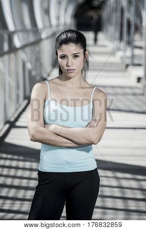 portrait of young beautiful and attractive hispanic brunette woman looking cool and defiant posing on urban metal city bridge after running workout in sport fitness and healthy lifestyle concept