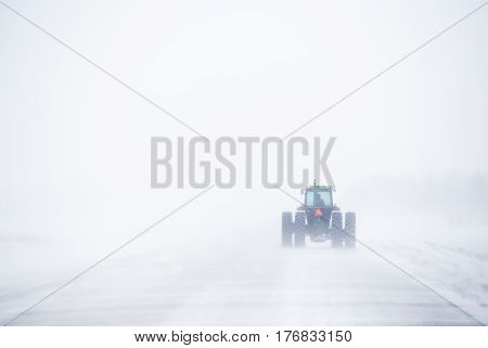 The backend of a farm tractor driving down a gravel road in a white winter blizzard