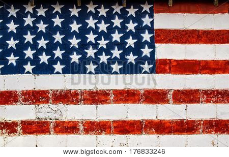 The red white and blue american flag painted on a cracked and weathered cement wall