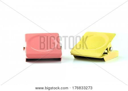 One pink and yellow metal clip on white background