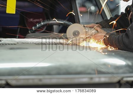 Worker works with angle grinder in a car repair shop