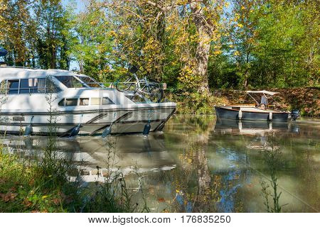 Poihes, France - October 4, 2016; Small boat and launch meet and navigate past in shady bend of Canal Du Midi Poihes France