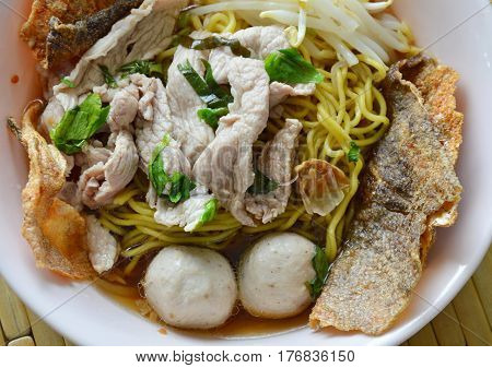 Chinese egg noodle with pork ball topping crispy fish skin in soup