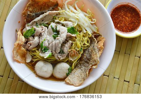 Chinese egg noodle with pork ball topping crispy fish skin in soup and chili sauce