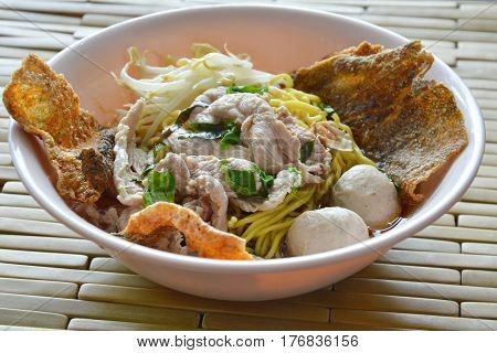 yellow noodle with pork ball topping crispy fish skin in soup